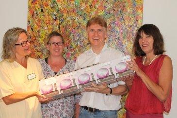 Dr. Beatrix Schmidt und zwei Pflegende nehmen die Spende von Jörg Brückner entgegen
